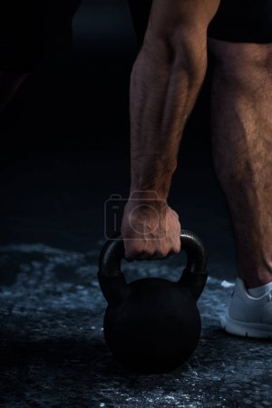 Photo for Cropped view of muscular bodybuilder excising with kettlebell on black - Royalty Free Image