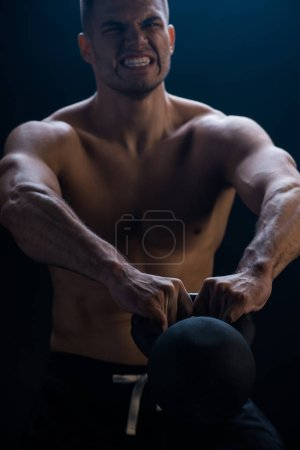 Photo for Tense sexy muscular bodybuilder with bare torso excising with kettlebell on black background - Royalty Free Image
