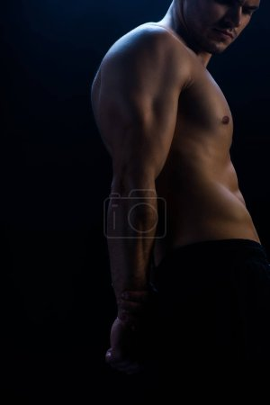 Photo for Cropped view of sexy muscular bodybuilder with bare torso on black background - Royalty Free Image