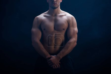 Photo for Cropped view of sexy muscular bodybuilder with bare torso posing on black background - Royalty Free Image