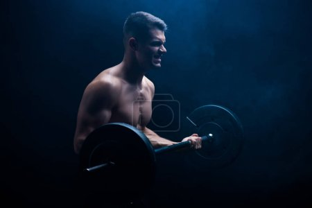 tense sexy muscular bodybuilder with bare torso excising with barbell on black background