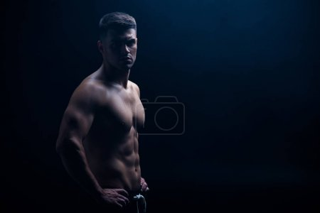 Photo for Sexy muscular bodybuilder with bare torso posing with hands on hips isolated on black - Royalty Free Image