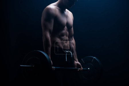 Photo for Cropped view of muscular bodybuilder with bare torso excising with barbell on black background - Royalty Free Image
