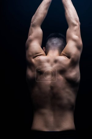 back view of sexy muscular bodybuilder with bare torso posing isolated on black