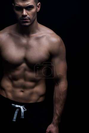 Photo for Sexy muscular bodybuilder with bare torso isolated on black - Royalty Free Image