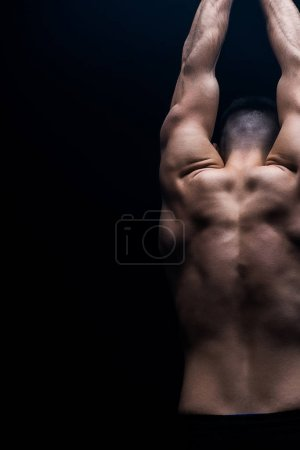 Photo for Back view of sexy muscular bodybuilder with bare torso posing isolated on black - Royalty Free Image