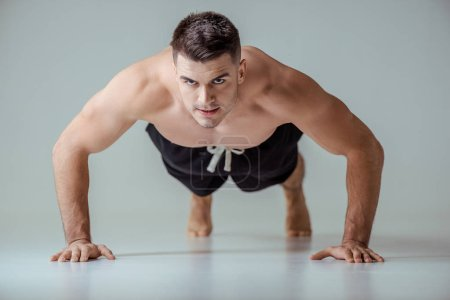 Photo for Sexy muscular sportsman with bare torso doing push ups on grey - Royalty Free Image