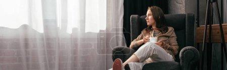 Photo pour Photo panoramique d'une jeune femme avec une jambe prothétique buvant du café dans un salon - image libre de droit