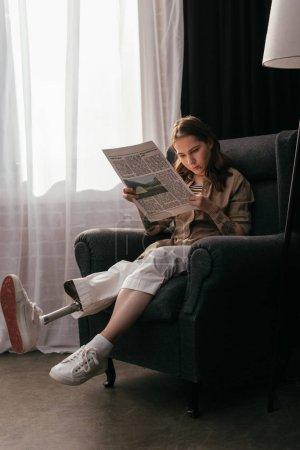 Photo pour Fille avec prothèse de jambe journal de lecture en fauteuil à la maison - image libre de droit