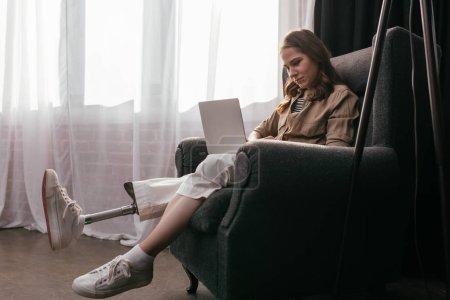 Photo pour Vue latérale d'une femme avec une jambe prothétique travaillant sur un ordinateur portable dans un salon - image libre de droit