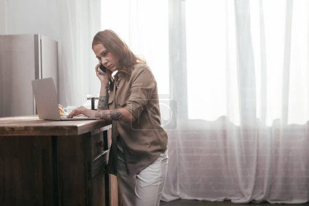 Photo for Young woman talking on smartphone and using laptop on kitchen table - Royalty Free Image