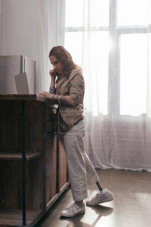 Photo pour Vue latérale d'une femme avec une jambe prothétique parlant sur un téléphone intelligent et travaillant sur une table de cuisine à l'ordinateur portatif - image libre de droit