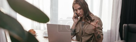 Photo for Selective focus of young woman talking on smartphone and looking at laptop at kitchen, panoramic shot - Royalty Free Image