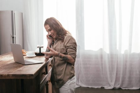 Photo for Side view of smiling woman talking on smartphone beside laptop on kitchen table - Royalty Free Image