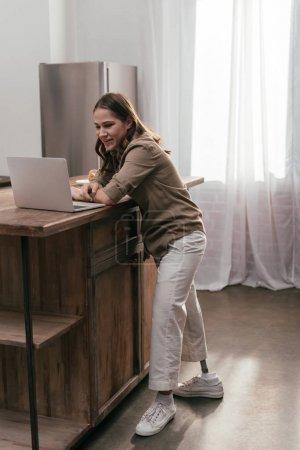 Photo pour Femme souriante avec jambe prothétique utilisant un ordinateur portable sur une table de cuisine - image libre de droit