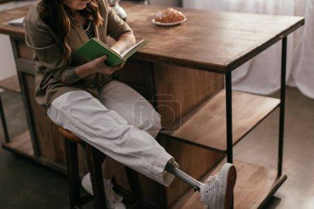 Photo pour Vue agrandie d'une fille avec un livre de lecture de prothèses à côté de la table à la maison - image libre de droit