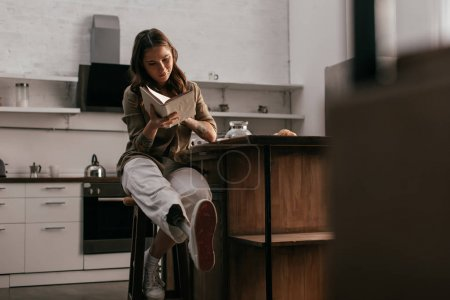Photo for Selective focus of girl with prosthetic leg reading book by kitchen table - Royalty Free Image