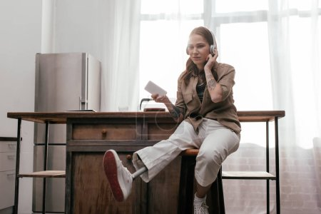 Photo for Young woman with prosthetic leg using headphones and holding smartphone be kitchen table - Royalty Free Image