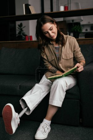 Photo for Beautiful young woman with prosthetic leg reading book on sofa in living room - Royalty Free Image