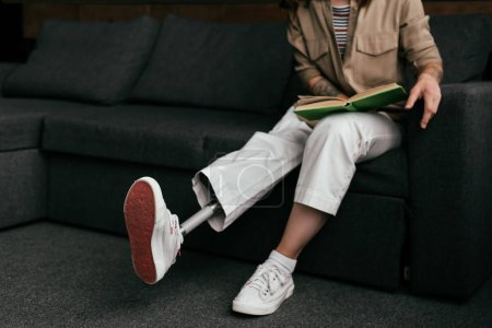 Photo for Cropped view of woman with leg prosthesis reading book on sofa - Royalty Free Image