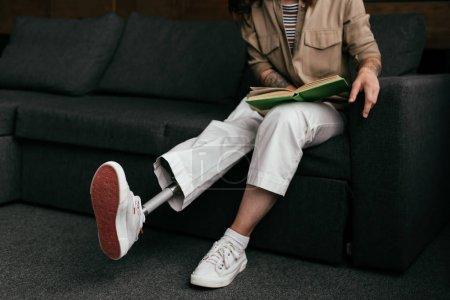 Photo for Cropped view of young woman with prosthetic leg reading book on sofa - Royalty Free Image