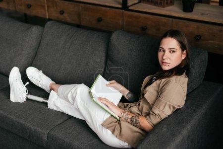 Photo pour Femme séduisante, tenant une jambe prothétique et regardant chez elle sur le canapé - image libre de droit