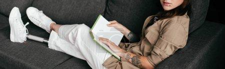 Photo pour Vue croustillante d'une femme tenant une jambe prothétique sur un canapé, prise de vue panoramique - image libre de droit