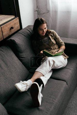 Photo pour Vue à grand angle d'une femme souriante avec un livre de lecture prothétique de jambes sur un canapé à la maison - image libre de droit