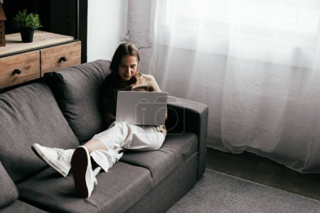 Photo for Selective focus of young woman with prosthetic leg using laptop on sofa at home - Royalty Free Image