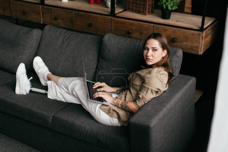 Photo for Young woman with prosthetic leg holding laptop and looking away on sofa - Royalty Free Image