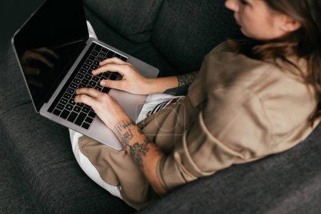 Photo pour Vue aérienne d'une femme utilisant un ordinateur portatif avec écran vierge sur un canapé, mise au point sélective - image libre de droit
