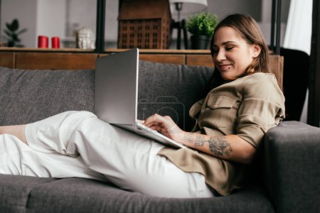 Photo for Side view of smiling woman using laptop on sofa in living room - Royalty Free Image