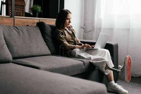 Photo for Young freelancer with leg prosthesis working at laptop on sofa in living room - Royalty Free Image