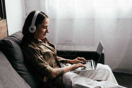 Photo pour Vue latérale du sourire freelancer dans les écouteurs travaillant à l'ordinateur portable sur canapé - image libre de droit