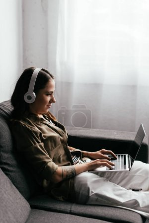 Photo for Side view of woman in headphones using laptop on sofa - Royalty Free Image
