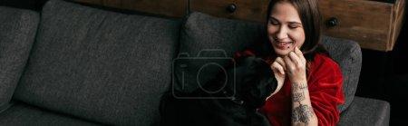 Photo for Panoramic shot of smiling girl looking at pug dog on sofa - Royalty Free Image