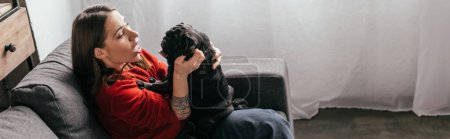 Photo for Side view of young woman playing with pug, panoramic shot - Royalty Free Image