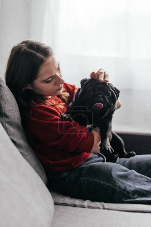 Photo for Side view of young woman stroking pug dog on sofa - Royalty Free Image
