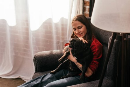 Photo for Cheerful woman with prosthetic leg petting pug dog in armchair at home - Royalty Free Image