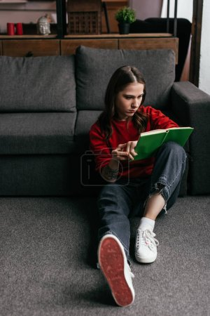 Photo for Attractive young woman reading book on floor beside sofa at home - Royalty Free Image