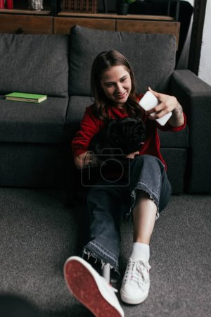 Photo for Girl with prosthetic leg holding pug and taking selfie with smartphone on floor in living room - Royalty Free Image