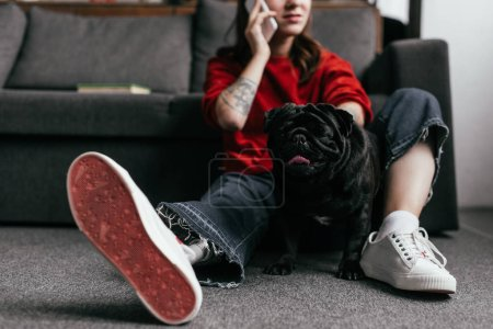 Photo for Cropped view of woman with leg prosthesis talking on smartphone beside pug on floor at home - Royalty Free Image