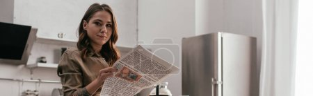 Photo for Panoramic shot of beautiful girl holding newspaper and looking at camera on kitchen - Royalty Free Image