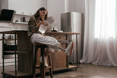Photo for Beautiful girl with prosthetic leg reading newspaper by kitchen table - Royalty Free Image