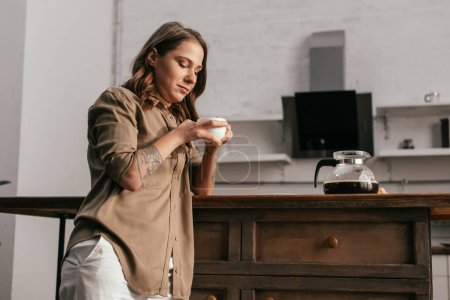 Photo for Beautiful young woman drinking coffee at kitchen - Royalty Free Image