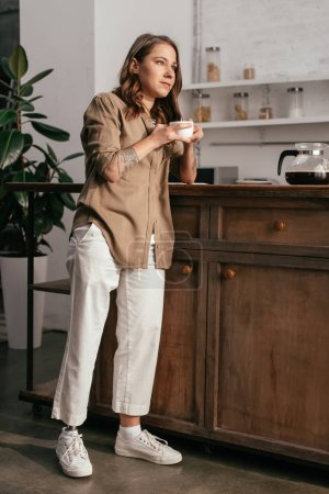 Photo for Young woman with prosthetic leg drinking coffee by kitchen table - Royalty Free Image