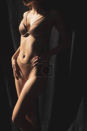 Photo pour Vue partielle de jeune femme sexy en sous-vêtements posant à la lumière du soleil sur fond avec draperie noire - image libre de droit