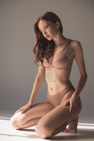 Photo pour Sexy fille en lingerie debout sur les genoux sur fond gris avec lumière du soleil - image libre de droit