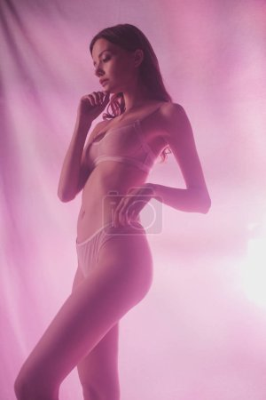 Photo for Sensual girl in lingerie holding hand near face while posing on pink and purple background with lighting - Royalty Free Image