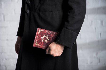 Photo pour Vue recadrée du jeune homme juif tenant le tanakh - image libre de droit